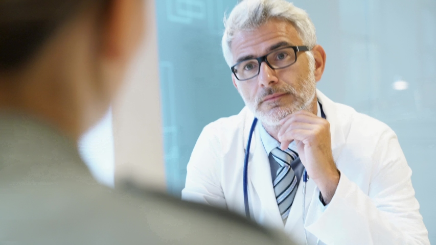 Mature doctor talking to patient in modern clinic | Shutterstock HD Video #1032056873