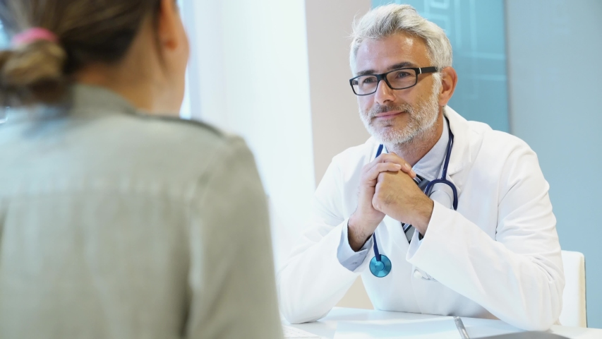 Mature doctor listening to patient in modern clinic | Shutterstock HD Video #1032056963