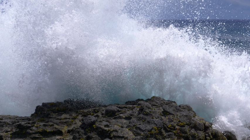 CLOSE UP: Big waves crash into the black volcanic rocks on the remote shore of Easter Island. Cinematic shot of a deep blue ocean swell violently splashing over the rocky coast of an exotic island. | Shutterstock HD Video #1032113483