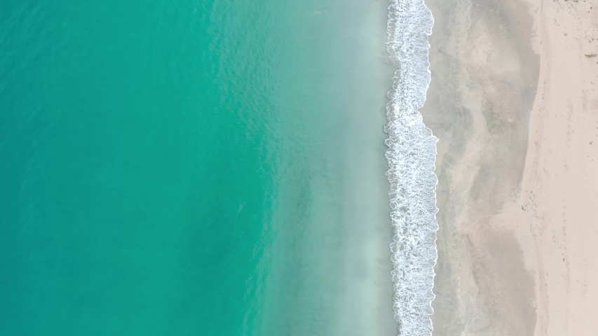 Tropical beach top view, waves break on tropical white sand beach top view. Caribbean sea waves seamless loop on amazing white sand beach. Video above turquoise blue sea water on the white sand shore. | Shutterstock HD Video #1032180503