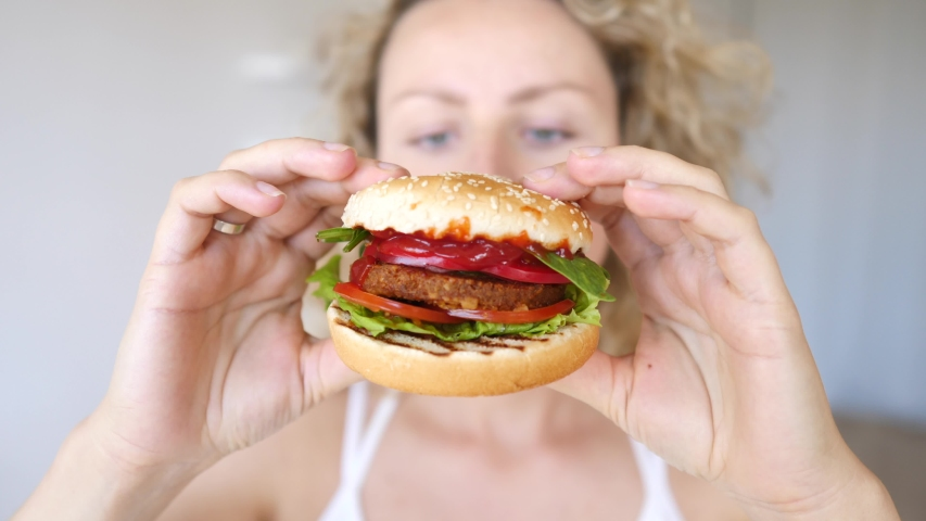 Young Woman Eating Vegan Hamburger. Junk Food Alternative, Healthy Fast Food Concept. | Shutterstock HD Video #1032228713