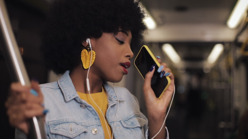 Portrait of young african american woman with headphones listening to music, sing and funny dancing in public transport. He holds the handrail. #1032279293