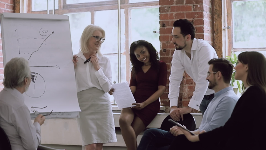 Old woman and man mentors teachers training young multiracial interns students group give flip chart presentation at corporate meeting, happy senior mid aged coaches teach diverse workers in office | Shutterstock HD Video #1032280133