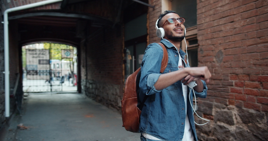 Slow motion portrait of Arabian guy in headphones dancing in the street holding modern smartphone having fun with gadgets. Melomaniacs and youth concept. #1032331373