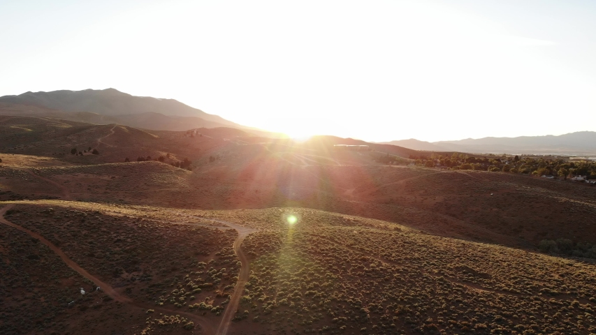 Dirt Bike Rides into Flared Sunset Leaving Dust Trail - Wide Aerial Drone.   Shutterstock HD Video #1032367913