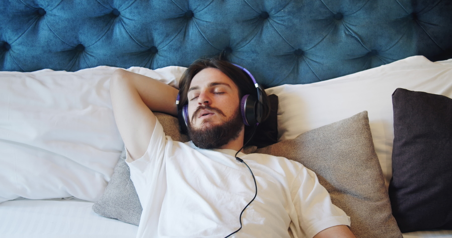 Handsome young man lying on bed in earphones and listening to favorite music, relaxation | Shutterstock HD Video #1032370133