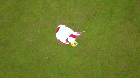 Drone shot, top view, of a red and white golf flag,ing in the wind, on a bright green golf field, on a sunny day