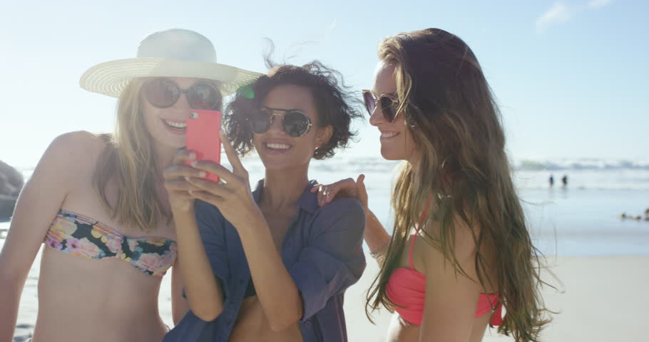Group of beautiful girl friends taking selfies on the beach on summer vacation using pink phone RED DRAGON