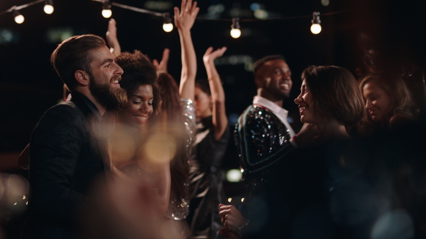 Fun party friends celebrating new years eve dancing throwing confetti enjoying glamorous celebration wearing stylish fashion social gathering on rooftop at night 4k | Shutterstock HD Video #1032521273