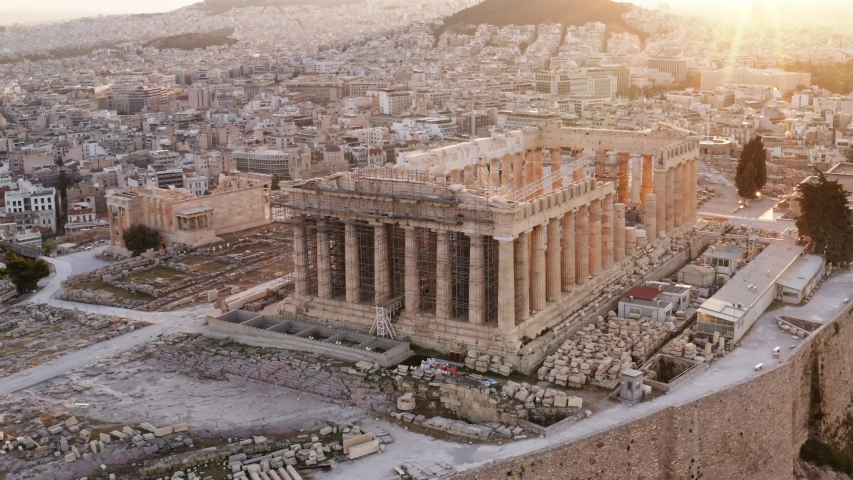 Aerial view of a slide from the drone on the panorama of residential buildings of the city of Athens, on the main symbol of ancient Greece, Acropolis at sunrise. The lights sun. World Heritage sites