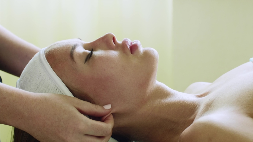 Beauty treatment in spa salon. Portrait of young woman is relaxing with close eyes on facial massage in cosmetology center, side view. Massage on face, neck and chest. | Shutterstock HD Video #1032532133