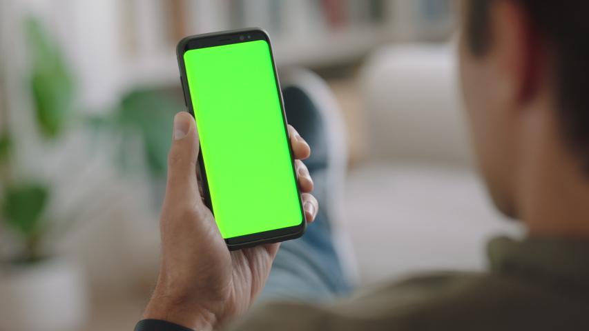 Young man using smartphone watching green screen enjoying entertainment on mobile phone chroma key display horizontal orientation 4k footage | Shutterstock HD Video #1032767453