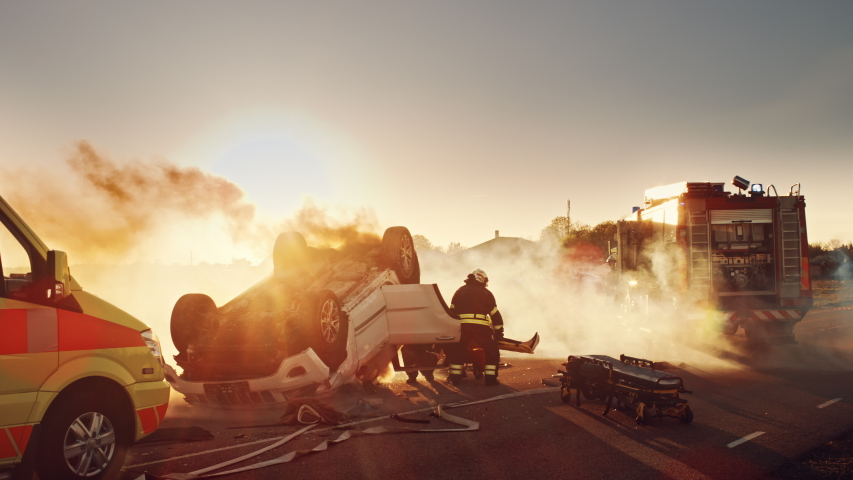 On the Car Crash Traffic Accident Scene: Rescue Team of Firefighters Pull Female Victim out of Rollover Vehicle, They Use Stretchers Carefully, Hand Her Over to Paramedics who Perform First Aid   Shutterstock HD Video #1032836363
