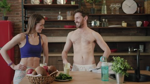 Shirtless handsome young man and slim sporty woman in cropped top compare their figures and abs. workout results, training, health, active lifestyle. Motivation and sport concept. Slow motion, close