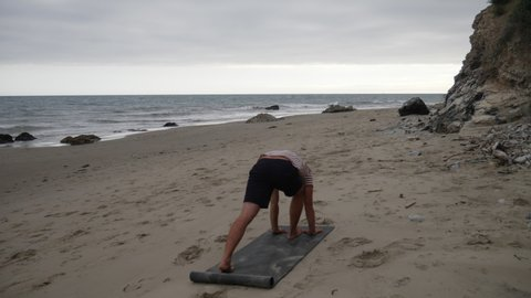 A man doing yoga on the beach to reduce stress near the calming ocean waves SLOW MOTION.