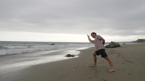 A young man doing yoga in cinematic slow motion on a beach with ocean waves in Santa Barbara, California.