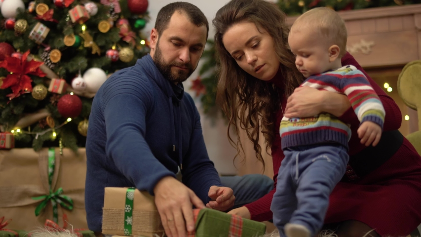 Mother, father and little baby sitting on the floor in the room with christmas decoration. Man gives small present box to child crawling on fluffy carpet. Happy family celebrating Christmas together