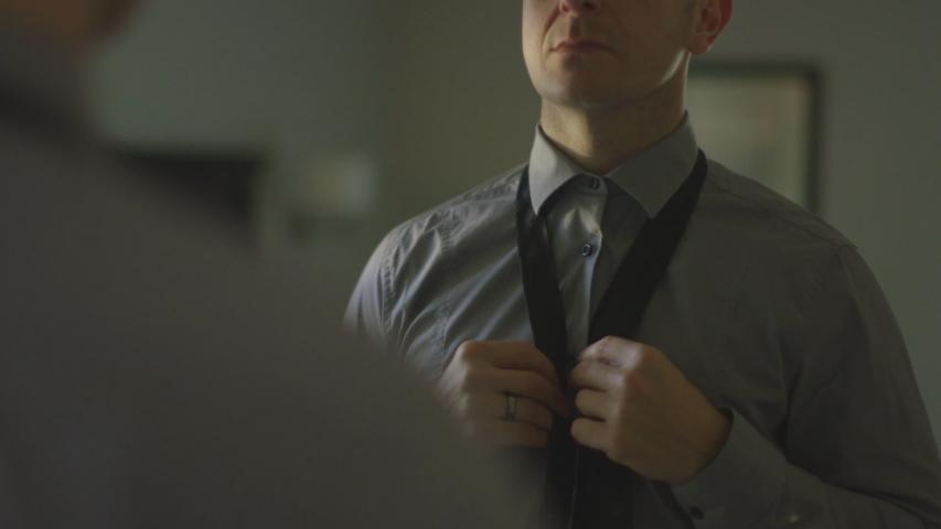 Caucasian man putting tie on at mirror