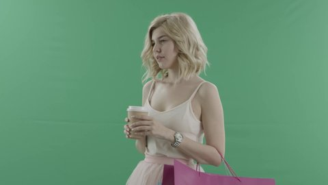 Woman with bags drinks coffee while waiting for someone against green screen