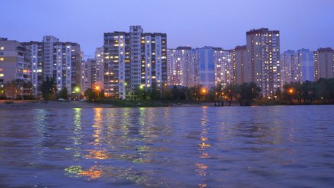 A complex of appartment buildings in the evening city near the large lake, with street lights reflecting in the water. Buildings in twilight near lake. Buildings and lights in appartments evening.