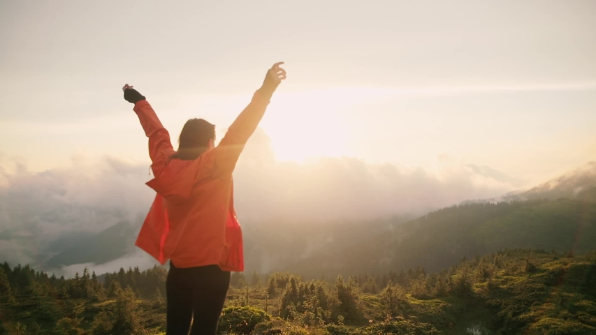 Camera follows hipster millennial young woman in orange jacket running up on top of mountain summit at sunset, jumps on top of rocks, raises arms into air, happy and drunk on life, youth and happiness | Shutterstock HD Video #1033184633