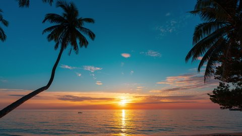 Colorful sunset on tropical beach with silhouette palm tree, crystal clear sea water and beautiful clouds on horizon.