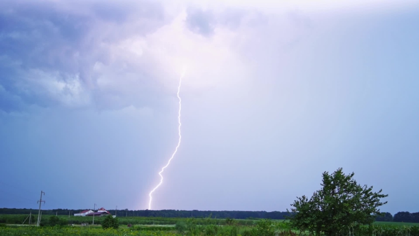 Bright lightning on the sky. Realistic view of direct lightning from sky to the ground in rural place. Dangerous time.