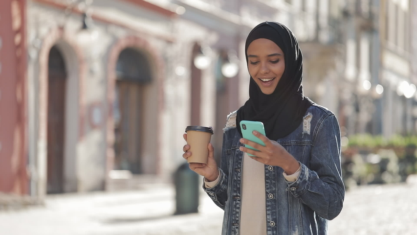 Young muslim woman wearing hijab headscarf walking in the city center, using smartphone and drinking coffee. Communication, online shopping, social network concept. | Shutterstock HD Video #1033256423