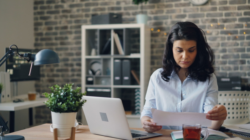 Office worker attractive young girl is reading paper document then using laptop typing working alone indoors. Business, information and workplace concept. | Shutterstock HD Video #1033273283