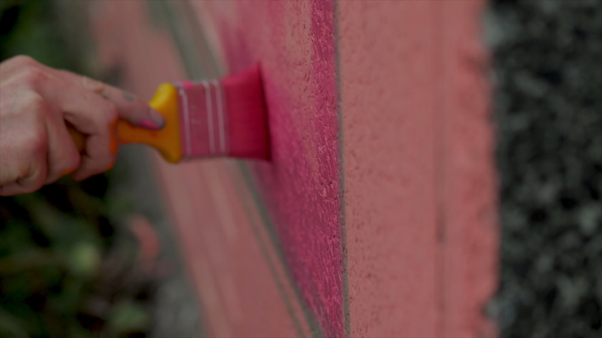 Painting a wall with paint brush close up. Artist applies paint on brick wall with a brush outside. Creating graffiti art close up. Painting art.  | Shutterstock HD Video #1033276883