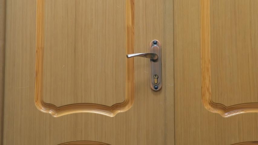 Wooden door with metal handle and lock indoors, closeup view. | Shutterstock HD Video #1033281263