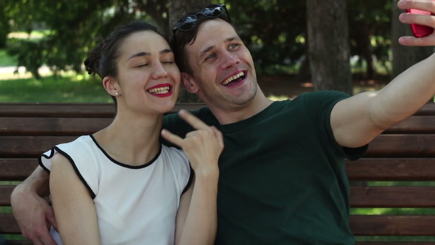 Young couple in love, on a sunny day, take a selfie while sitting on a bench in the park. They are smiling and hugging each other. | Shutterstock HD Video #1033281863