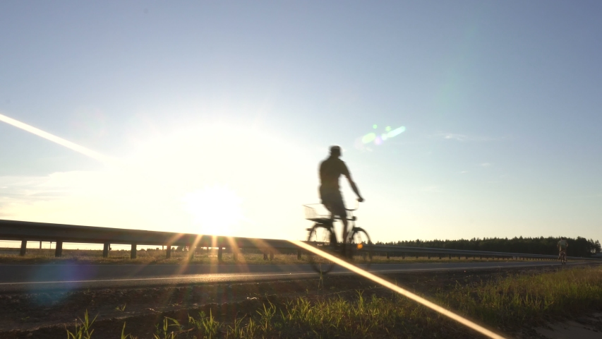 A child with his father riding a bike on the road against the backdrop of a sunset, travel and vacation concept, copy space #1033294043