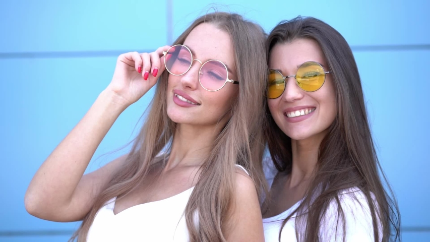 Two young beautiful smiling hipster girls in trendy summer colorful neon sunglasses. Women posing near blue wall | Shutterstock HD Video #1033376903