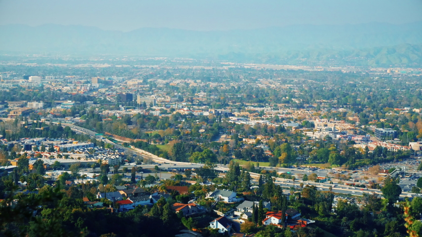 View of the city with green spaces. Green mountains in the city with a lot of beautiful trees. Freeway aerial view. Breathtaking look at busy city from the hills. Overlook in slow motion.