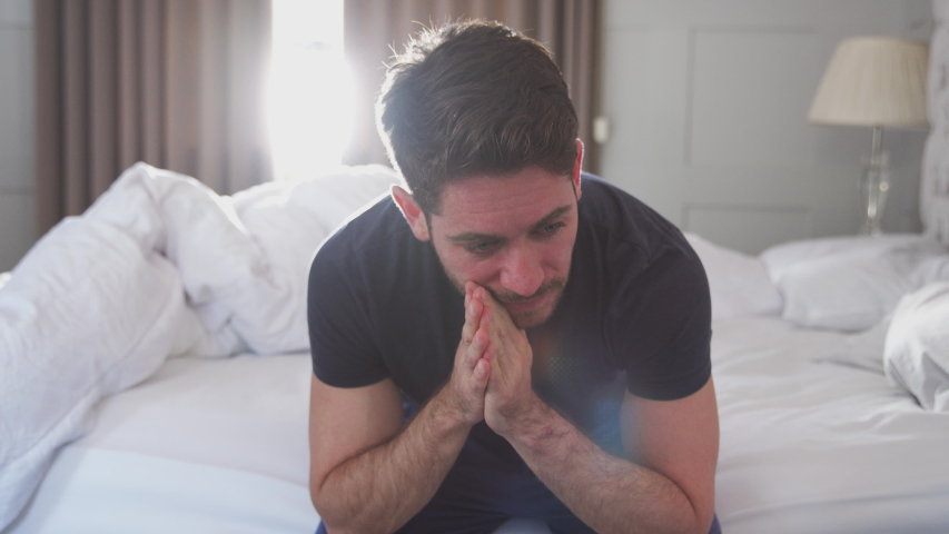 Man Wearing Pajamas Suffering With Depression Sitting On Bed At Home #1033470113