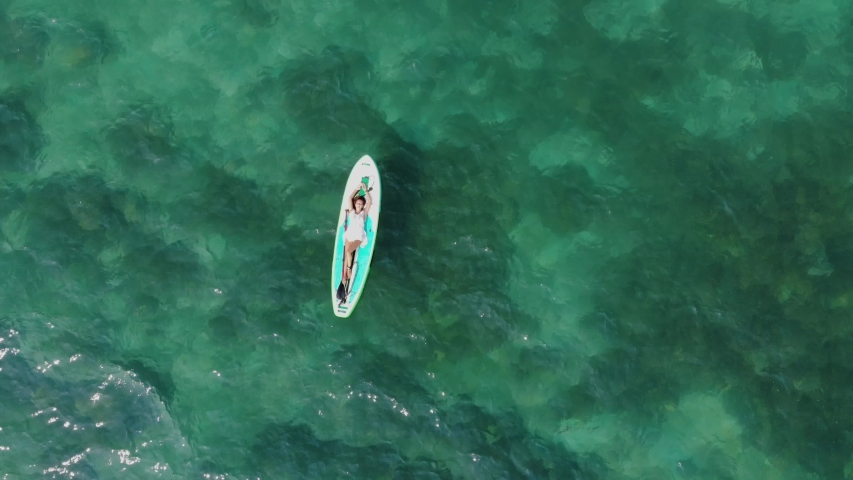 The woman on a board with an oar, SUP, swims in the sea, shooting from air | Shutterstock HD Video #1033474223