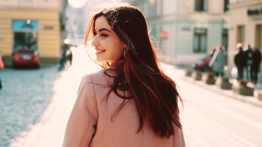 Shot behind a girl walking back head looks at camera smile at city center feel happy sunset fashion girl summer face technology sun beautiful portrait close up slow motion #1033560353