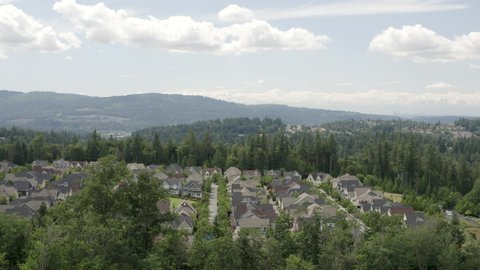 Issaquah Highlands Washington Aerial View New Homes Surrounded by Natural Beauty of Nature Forest Hillside and Seattle Skyline Background