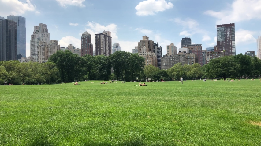 NEW YORK CITY crowd on a sweltering hot summer day in Central Park in New York. Central Park is a public park at the center of Manhattan that opened in 1857, on 778 acres of city-owned land. | Shutterstock HD Video #1033618403
