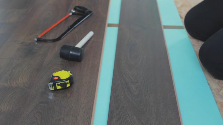 Builder renovating apartment. Works man installs laminate. Repair of the apartment, laying laminate flooring. Construction.   Shutterstock HD Video #1033649513