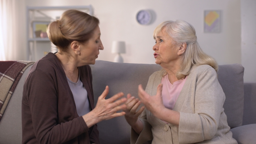 Self-assertive old women arguing and offending each other sitting in living room | Shutterstock HD Video #1033703633