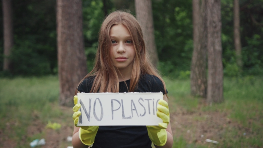 Save the planet for future. Portrait of a sweet teen girl showing a sign protesting against plastic pollution in the forest. No plastic concept. Eco-friendly environment.   Shutterstock HD Video #1033742243