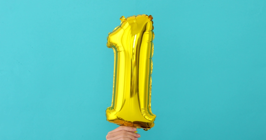 Gold foil number 1 one celebration balloon on blue background   Shutterstock HD Video #1033864823