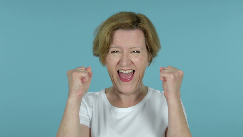 Old Woman Celebrating Success Isolated on Blue Background | Shutterstock HD Video #1033902053