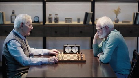 side view of two pensive senior men sitting at table, playing chess and pressing button on chess clock in living room