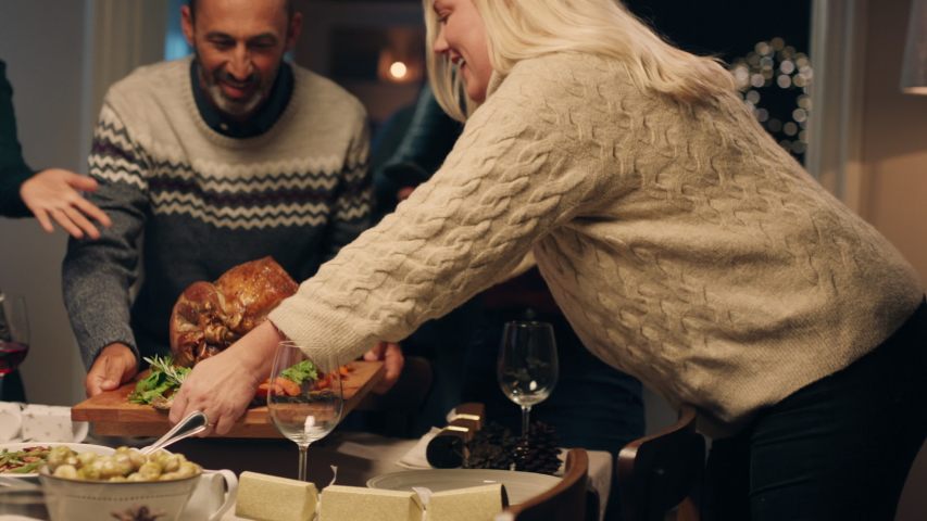 Christmas family preparing dinner table with turkey friends arriving for dinner party celebrating festive holiday reunion enjoying feast at home 4k footage | Shutterstock HD Video #1033930553