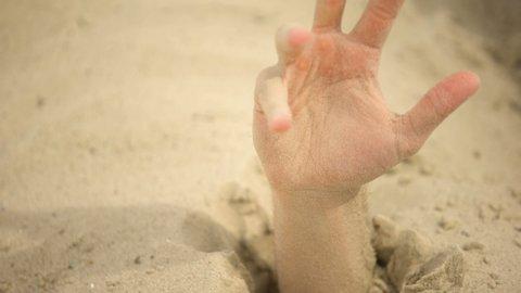 Hand desperately waving, sinking in quicksand, trapped tourist in desert, danger