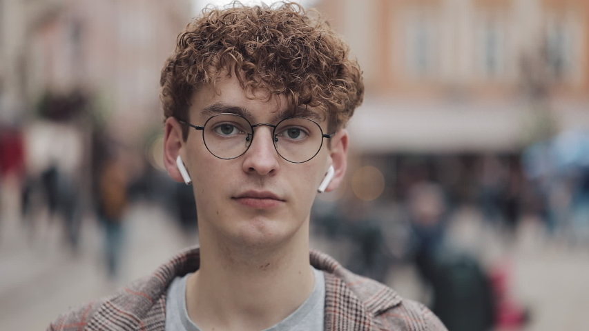 Portrait of young hipster guy with wireless earphones standing on the city street and looking into the camera. Tourist, travel, student concept. Urban lifestyle. | Shutterstock HD Video #1034020793