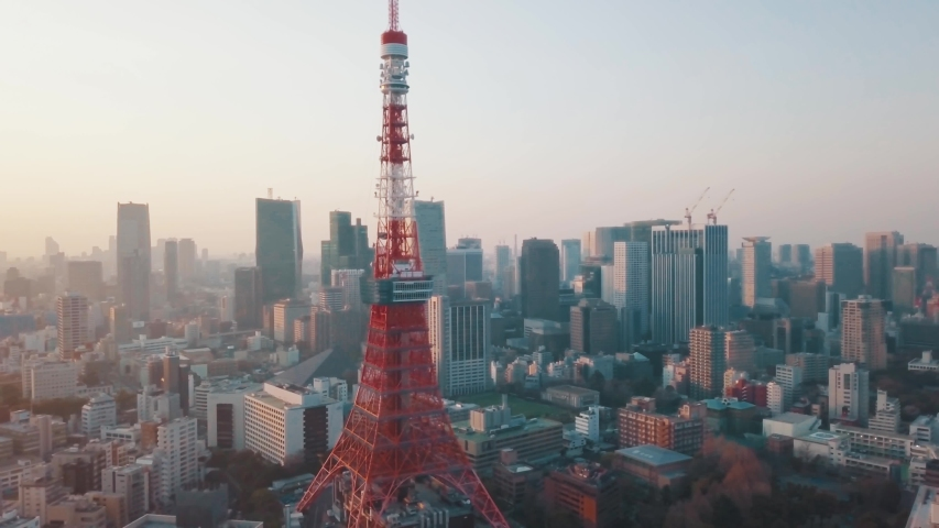 Drone aerial above Tokyo City panning around the iconic red Tokyo Tower surrounded by tall skyscrapers during a stunning sunset with blue and orange skies | Shutterstock HD Video #1034022323